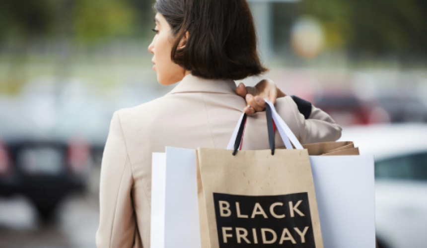 "Shopper holding a bag labeled ""Black Friday"""