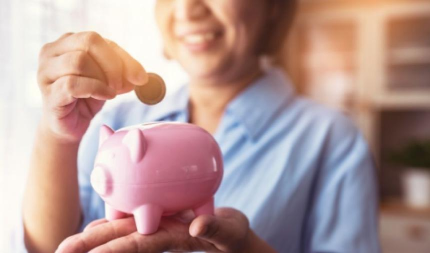 Woman holding a piggy bank in the foreground.