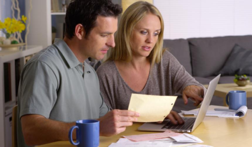 husband and wife baying bills on laptop