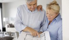 Older couple looking at plans to renovate their home.