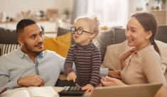 Husband and wife interrupted by cute baby while working on finances