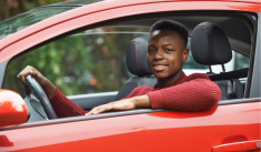 Young man smiling in the driver's seat of a car.