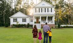 family looking at new home in front yard