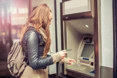 Lady at a stand-a-lone ATM getting money